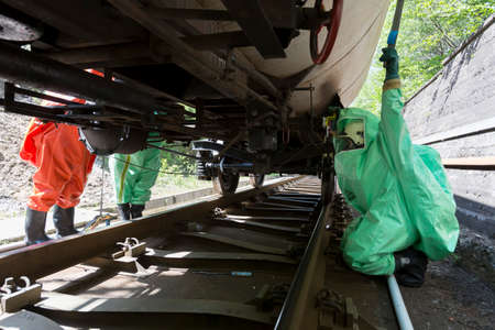 A team working with toxic acids and chemicals is securing a chemical cargo train tanks crashed near Sofia, Bulgaria. Teams from Fire department are participating in an emergency training with spilled toxic and flammable materials. photo