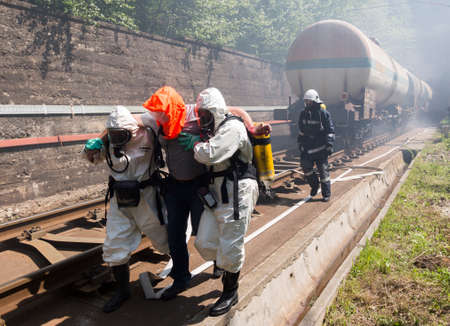 riesgo quimico: Sofía, Bulgaria - 19 de mayo 2015: Un equipo que trabaja con ácidos tóxicos y productos químicos está salvando a gente de un choque de trenes de carga química. Los equipos de bomberos están participando en un entrenamiento de emergencia con materiales tóxicos e inflamables derramados.