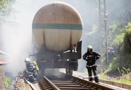 fatality: Sofia, Bulgaria - May 19, 2015: Firefighters are extinguishing chemical cargo train tanks near Sofia. Teams from Fire department are participating in an emergency training with spilled toxic and flammable materials.