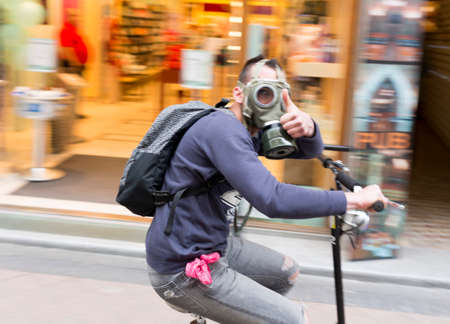 two wheel: Budapest, Hungary - April 30, 2015: An young Hungarian boy with gas mask is driving a two wheel scooter in a central street in Budapest.