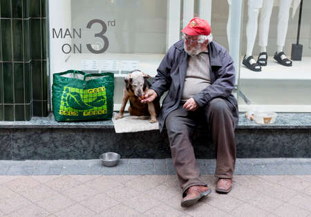 Budapest, Hungary - April 30, 2015: An old man is begging in front of a fashion shop in a main street in Budapest, Hungary. 新聞圖片
