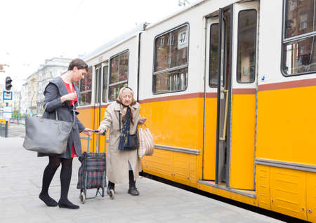 mixed age range: Budapest, Hungary - April 30, 2015: An young woman is helping an old lady to get on the trolley car number 47 at its last staition in Budapest, Hungary
