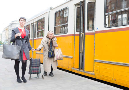 active adult community: Budapest, Hungary - April 30, 2015: An young woman is helping an old lady to get on the trolley car number 47 at its last staition in Budapest, Hungary