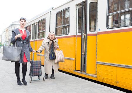 person traveling: Budapest, Hungría - 30 de abril 2015: Una mujer joven está ayudando a una anciana para conseguir en el número tranvía 47 en su última staition en Budapest, Hungría Editorial