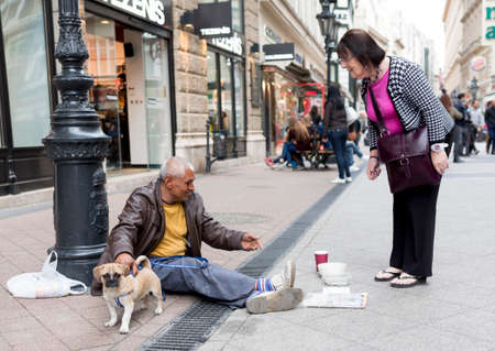Boedapest, Hongarije - 30 april 2015: Een oude man is bedelen voor een modewinkel in een doorgaande straat in Boedapest, Hongarije. Redactioneel