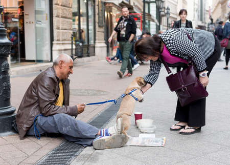 help: Budapest, Hungary - April 30, 2015: An old man is begging in front of a fashion shop in a main street in Budapest, Hungary. Editorial
