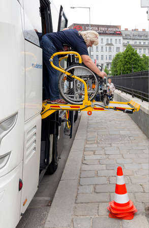 1 person: Vienna, Austria - May 1, 2015: A bus assistant is preparing accessibility platform for physically disabled person in a wheelchair to board in the bus. Editorial