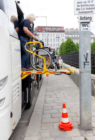 physically: Vienna, Austria - May 1, 2015: A bus assistant is preparing accessibility platform for physically disabled person in a wheelchair to board in the bus. Editorial