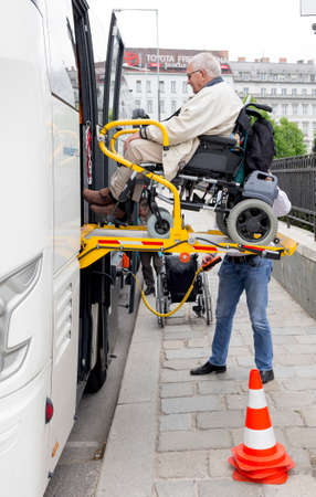 helps: Vienna, Austria - May 1, 2015: A bus driver helps physically disabled person in a wheelchair to board in the bus.