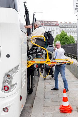 paraplegico: Viena, Austria - 01 de mayo 2015: Un conductor de autobús ayuda a personas con discapacidad física en silla de ruedas para embarcar en el autobús.