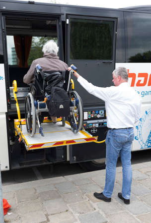 Vienna, Austria - May 1, 2015: A bus driver helps physically disabled person in a wheelchair to board in the bus.