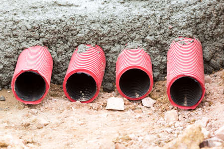 concreting: Concreting red corrugated pipes for electrical installation.