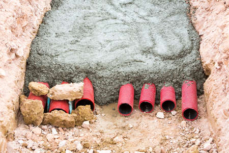 plastic conduit: Concreting red corrugated pipes for electrical installation.