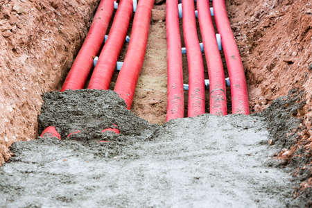 Concreting red corrugated pipes for electrical installation.
