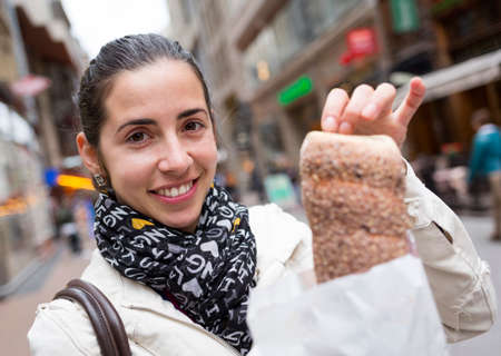 culinary tourism: An young woman with chimney cake (Kurtos Kalacs) at a main steet in Budapest, Hungary.