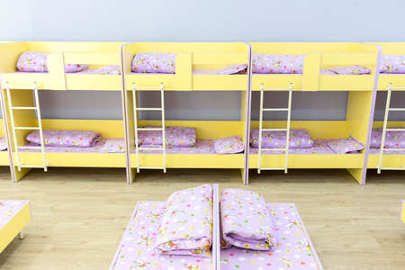bunkbed: Modern kindergarten bedroom with small bunk beds with stairs for the kids.