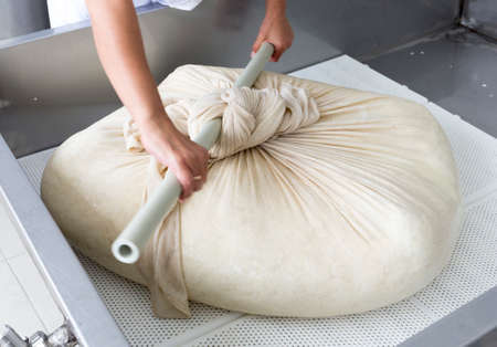 cabras: Una mujer que trabaja en una pequeña lechería familiar está procesando los pasos finales de hacer un lote de queso. La granja de productos lácteos está especializada en yogur búfalo y la producción de queso.