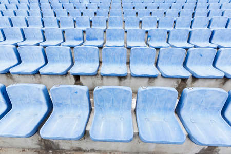 replacement: Many blue old seats at a stadium which need replacement.