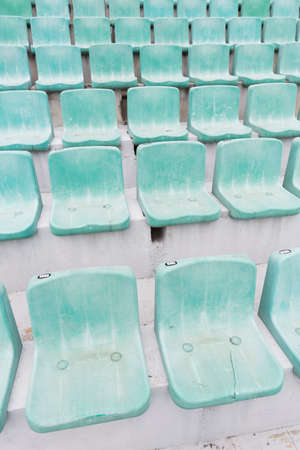 replacement: Many green old seats at a stadium which need replacement. Stock Photo
