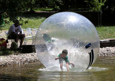 bola de billar: Sofia, Bulgaria - 14 de junio 2015: Un ni�o est� jugando en una gran esfera de pl�stico inflable en un peque�o lago en el parque gradina Borisova de Sof�a. Editorial