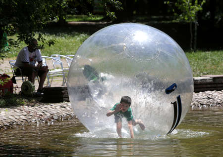 ball: Sofia, Bulgaria - June 14, 2015: A child is playing in a big inflatable plastic sphere in a small lake in Sofias Borisova gradina park.