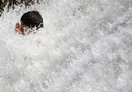 man waterfalls: Sofia, Bulgaria - June 15, 2015: An young man is cooling down in a small waterfall in a hot summer day near Sofia.
