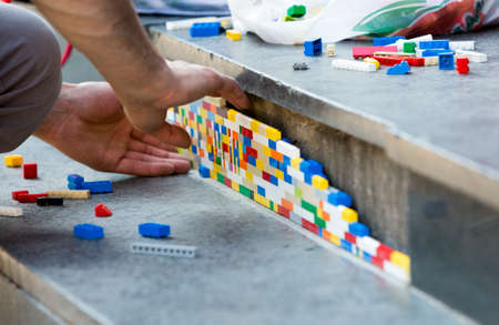 Sofia, Bulgaria - June 6, 2015: The artist Jan Vormann is filling the cracks in the exterior of a building in Sofia with Lego blocks as part of a city art festival.