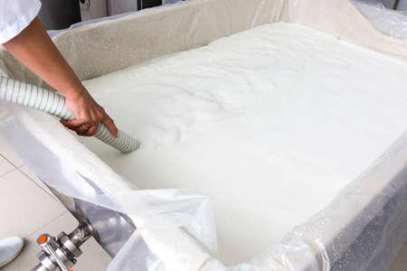 vacas lecheras: Queso tanque de producci�n mientras se llena con leche de b�fala en una peque�a lecher�a familiar. La granja de productos l�cteos est� especializada en yogur b�falo y la producci�n de queso.
