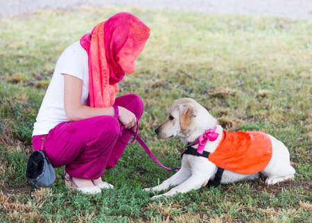 using senses: A trainer is standing beside a golden retriever guide dog during the last training for the animal. The dogs are undergoing various trainings before finally given to a blind person.