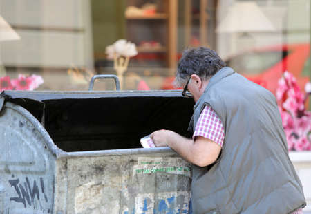 dependency: Sofia, Bulgaria - June 10, 2015: A man is digging into a recycle bin in a main street in Sofia. Years after joining the EU many Bulgarians are still living under the poverty line.