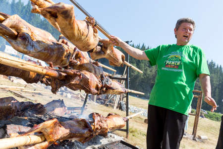 Rojen, Bulgaria - July 19, 2015: A cooker is preparing a traditional Bulgarian roasting lamb barbecue. It is roasted meat over an open fire, cooked in a special way. Éditoriale