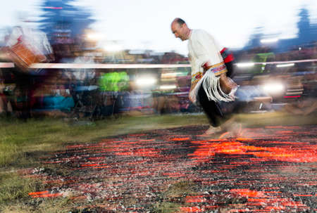 involves: Rozhen, Bulgaria - July 18, 2015: A nestinar is walking on fire during a nestinarstvo show. The fire ritual involves a barefoot dance on smouldering embers performed by nestinari.
