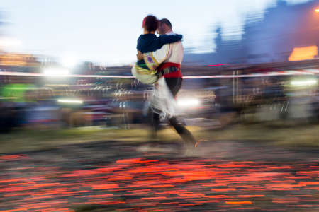 involves: Rozhen, Bulgaria - July 18, 2015: A nestinar with a child is walking on fire during a nestinarstvo show. The fire ritual involves a barefoot dance on smouldering embers performed by nestinari. Editorial