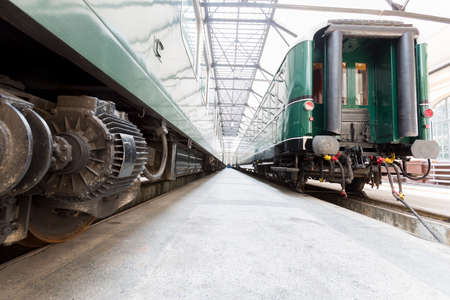 heavy risk: Old authentic green passenger trains in a depot for renovation before being used for tourist trips across Europe. Details of the trains transmission.