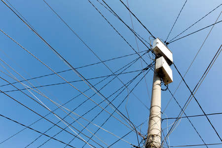 power pole: Power pole with white boxes with many electric cables in gypsy neighborhood in Sofia, Bulgaria. Stock Photo