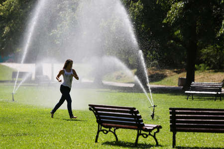 bulgaria girl: Sofia, Bulgaria - August 7, 2015: An young girl is running through the spray of watering systems water in the Borisova gradina park in Sofia. Editorial