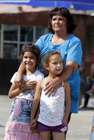 uneducated: Sofia, Bulgaria - July 30, 2015: Gypsies children with their grandmother are attending at the official opening of a center in their neighborhood for mothers and children in risk. Editorial