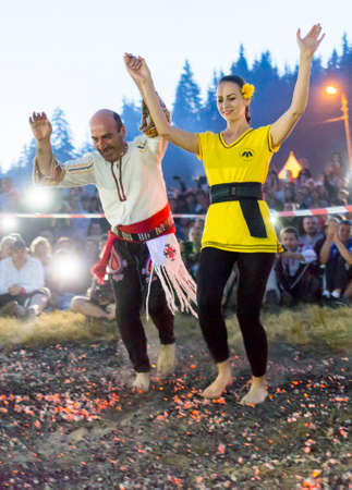 involves: Rijen, Bulgaria - July 18, 2015: A nestinar woman with a child is walking on fire during a nestinarstvo show. The fire ritual involves a barefoot dance on smouldering embers performed by nestinari. Editorial