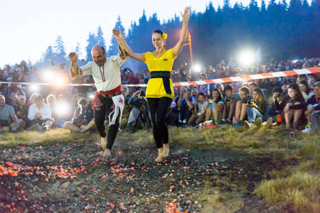Rijen, Bulgaria - July 18, 2015: A nestinar woman with a child is walking on fire during a nestinarstvo show. The fire ritual involves a barefoot dance on smouldering embers performed by nestinari. Editorial