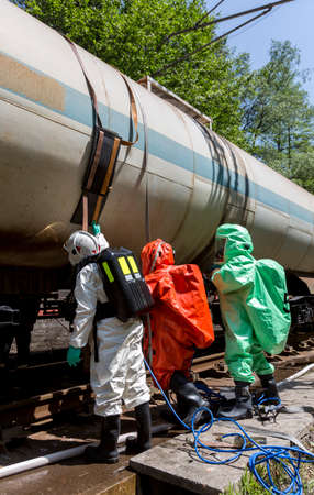 safety mask: A team working with toxic acids and chemicals is securing a chemical cargo train tanks crashed near Sofia, Bulgaria. Teams from Fire department are participating in an emergency training with spilled toxic and flammable materials.
