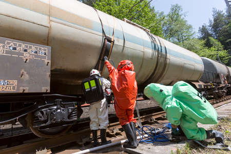 A team working with toxic acids and chemicals is securing a chemical cargo train tanks crashed near Sofia, Bulgaria. Teams from Fire department are participating in an emergency training with spilled toxic and flammable materials. Reklamní fotografie - 44224149