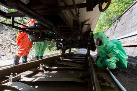 Un equipo que trabaja con ácidos tóxicos y productos químicos es asegurar una químicas tanques del tren de carga se estrelló cerca de Sofía, Bulgaria. Los equipos de bomberos están participando en un entrenamiento de emergencia con materiales tóxicos e inflamables derramados.