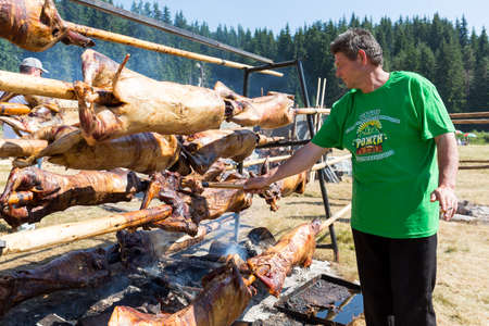 slasher: Rozhen, Bulgaria - July 19, 2015: A cook is preparing traditional Bulgarian barbecue of roasted meat over an open fire, prepared in a special way at a folklore festival. Editorial