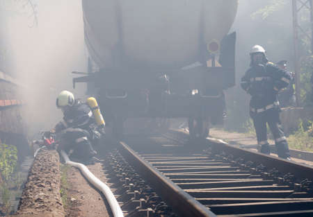 Sofia, Bulgaria - May 19, 2015: Firefighters are extinguishing chemical cargo train tanks near Sofia. Teams from Fire department are participating in an emergency training with spilled toxic and flammable materials.