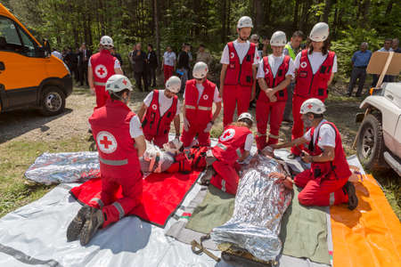 first aid kit: Sofia, Bulgaria - May 19, 2015: Volunteers from Bulgarian Red Cross organization are participating in a training with Fire department. They are assisting first aid to people involved in a train crash accident.