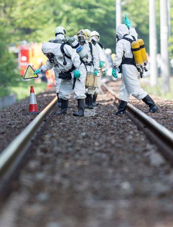 riesgo quimico: Sof�a, Bulgaria - 19 de mayo 2015: Un equipo que trabaja con �cidos t�xicos y productos qu�micos se acerca a un accidente qu�mico tren de carga cerca de Sof�a. Los equipos de bomberos est�n participando en un entrenamiento de emergencia con materiales t�xicos e inflamables derramados.