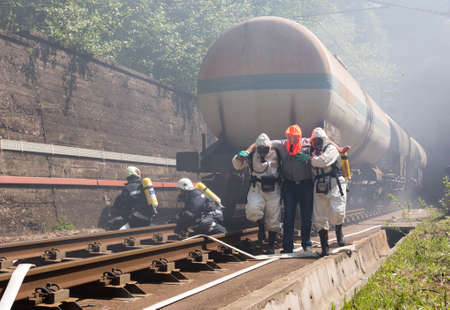 Sofia, Bulgaria - May 19, 2015: A team working with toxic acids and chemicals is saving people from a chemical cargo train crash. Teams from Fire department are participating in an emergency training with spilled toxic and flammable materials. 新闻类图片