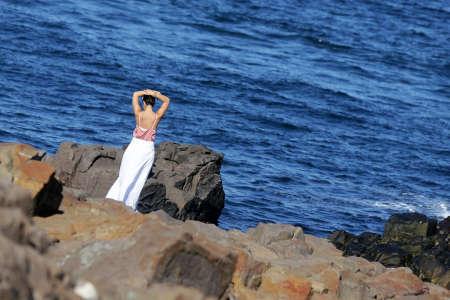 bulgaria girl: A woman in white dress is enjoying the Black sea feom the rocks at the coast of Sozopol, Bulgaria