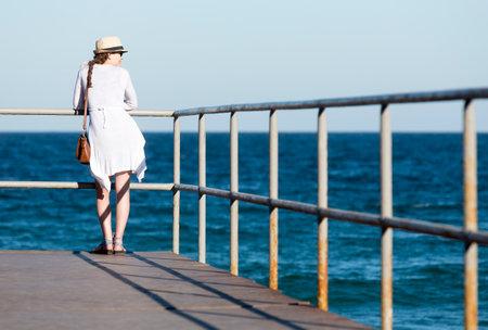mujer mirando el horizonte: Sozopol, Bulgaria - 1 de septiembre de 2015: Una mujer joven está mirando las aguas del mar Negro desde un muelle en Sozopol, Bulgaria.