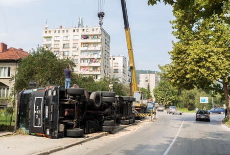 troyan: Troyan, Bulgaria - September 22, 2015: А crane machine is drawing the cargo tank of an overturned truck near the main street of a small town.